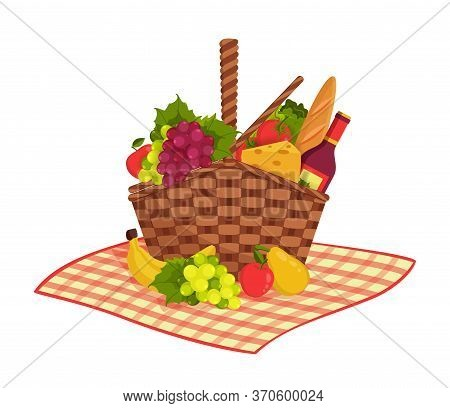 Wicker Picnic Basket Full Of Healthy Food On Picnic Blanket. Bottle Of Wine, Apple, Pear, Cheese, Ba