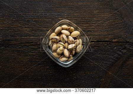 Pistachios In A Small Plate On A Vintage Wooden Table. Pistachio Is A Healthy Vegetarian Protein Nut
