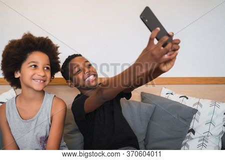 Portrait Of Two Afro American Brothers Taking A Selfie With Mobile Phone At Home. Lifestyle And Tech