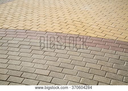 View Of The Sidewalk Paved With Rectangular Paving Stones In A Semicircle Of Yellow Lilac-gray Color