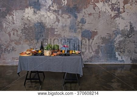 Stand-up meal with tasty food and drinks on tablecloth. Table placed in an industial interior with textured wall with copy space