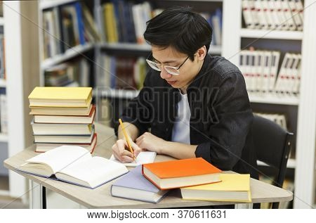 Academic Assignment. Japanese Boy In Specs Sitting In Public Library, Writing In Notepaper, Free Spa