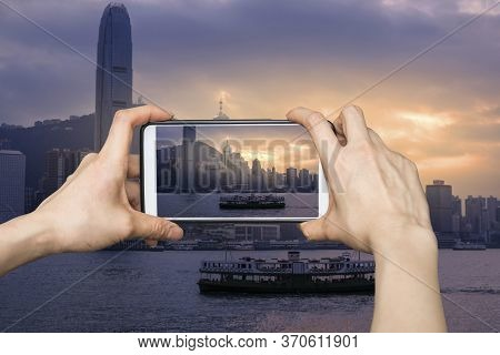 Girl Taking Pictures On Mobile Smart Phone In Hong Kong's Victoria Harbour In Sunrise