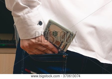 A Man Puts In His Back Pocket Jeans A Pack Of Hundred-dollar Bills In A White Shirt In The Office