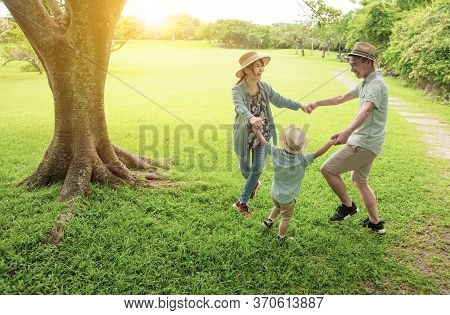 Happy Asian Family Playing Together At  Park