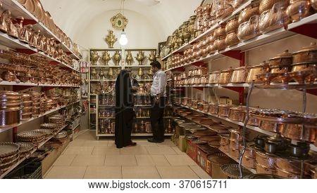 Yazd, Iran - 2019-04-11 - Customer Shops In A Copper Ware Vendor Shop.