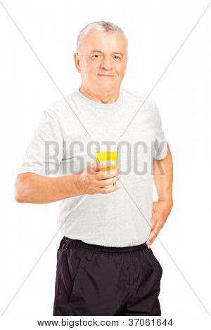 Mature athlete holding a glass of orange juice, refreshing after an exercise, isolated on white background