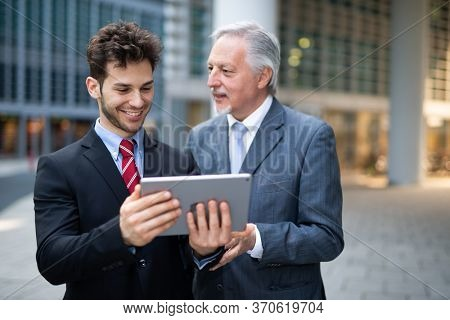 Business people working on a tablet outdoor