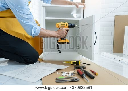 Close Up Man Holding Cordless Screwdriver Machine And Screws Lie For Screwing A Screw Assembling Fur