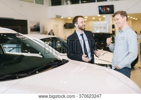 Cheerful Customer And Friendly Salesman Wearing Business Suit Conversation New Car In Auto Dealershi