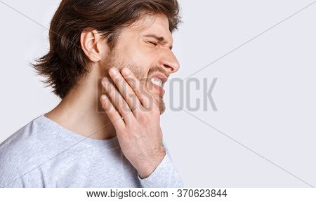Not Tolerate Pain In Teeth And Dentures. Man Suffers From Pain And Presses His Hand To Cheek, Panora