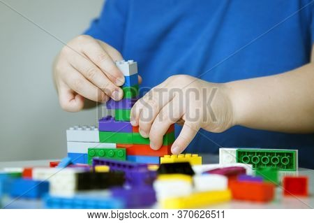 Close Up Of Child's Hands Playing With Colorful Plastic Bricks At The Table. Toddler Having Fun And