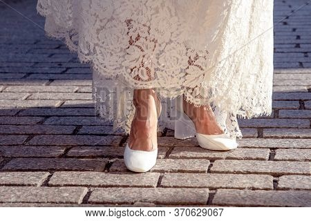 Bride Showing Her  Beautiful Shoes Against The Background Of Paving Stones