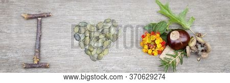 Top View On Autumn Colorful Composition From Nuts, Seeds ( In Heart Shape),  Sticks And Flowers Lyin