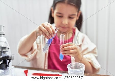The Scientist Kid Testing Chemistry Lab Experiment With A Microscope In The School. Little Girl Look