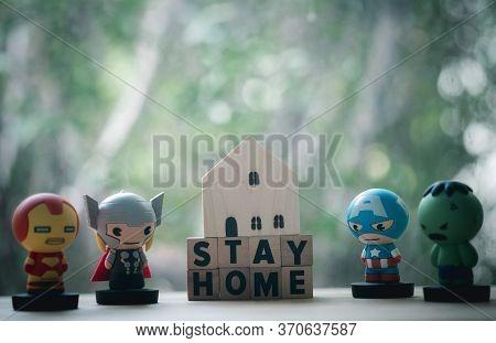 Bangkok, Thailand - June 10, 2020: Superhero With Miniature Wood Home. Concept Of Hero At Home. Conc