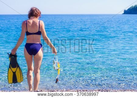 Woman Back View With Snorkel Equipment Flippers And Snorkeling Mask Tube On Beach Sea Shore. Summer