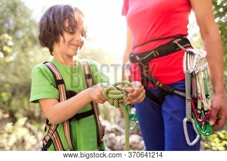 A Child Learns To Knit The Safety Knot From The Rope. Climbing Rope For Belaying. A Little Boy Is Tr