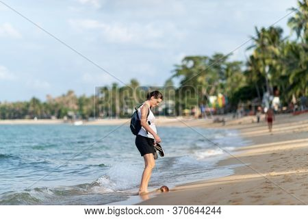 pregnant woman walking along the beach