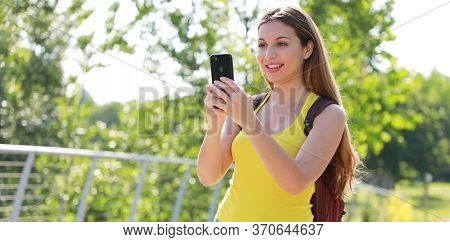 Relaxed Female Hiker Checking Gps Coordinates With Her Smart Phone Looking For The Right Direction.