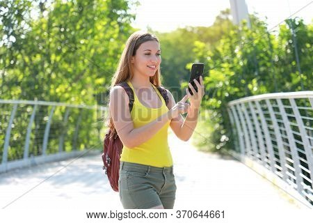 Young Backpacker Girl Checking Gps Coordinates With Her Mobile Phone In Natural Park. Ecological Tou