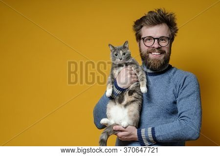 Shaggy, Happy Man With Glasses Hugs His Adorable Cat. Copy Space. Concept Of Love For Pets.