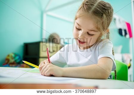Adorable Toddler Girl Drawing With Pencils At Home Sitting At The Table. Creative Child Sitting In A