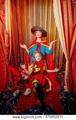 Family During A Stylized Theatrical Circus Photo Shoot In A Beautiful Red Location. Models Grandmoth