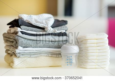 A Pile Of Baby Clothes, Disposable Diapers And A Feeding Bottle. Parenting Expenses Concept. Working