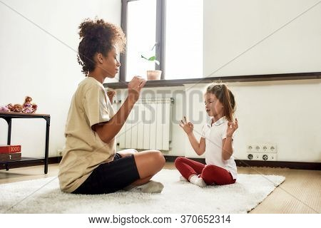 Full Length Shot Of African American Woman Baby Sitter And Caucasian Cute Little Girl Doing Yoga At