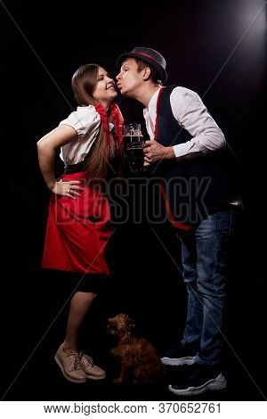 Funny Oktoberfest Couple In National Ethnic Dress With Mugs Of Beer, Small Shaggy Dog Kisssing On Bl