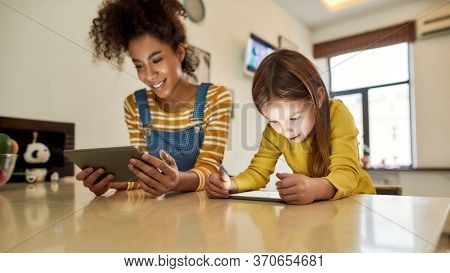 African American Woman Baby Sitter And Caucasian Cute Little Girl Reading, Using Tablet Pc, Sitting