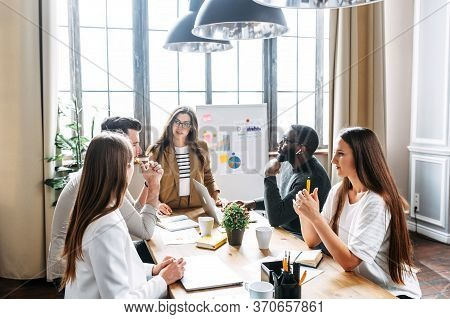 Multiracial Team. A Group Of Ambitious Young People In Smart Casual Wear Discuss Business Tasks Sitt