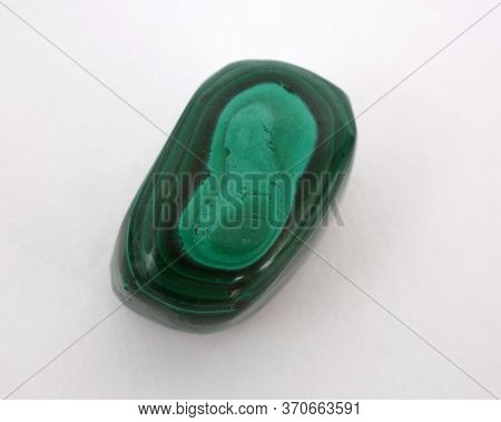 A Malachite Gemstone Photographed Against A White Background