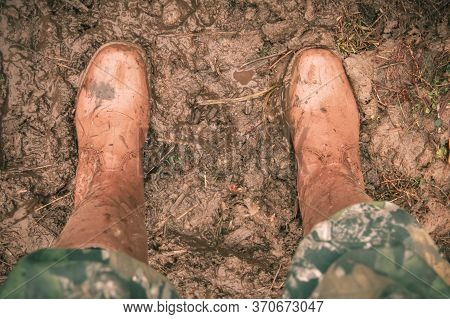 Boots In The Mud Top View. The Mans Feet, Shod In Brown Waterproof Rubber Boots And A Protective Sui