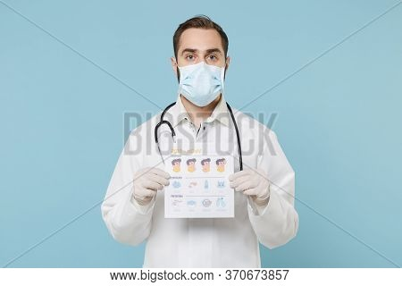 Male Doctor Man In Medical Gown Face Mask Gloves Isolated On Blue Background. Epidemic Pandemic Coro