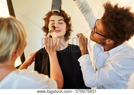 Hairstylist and make-up artist make-up model before a photo shoot