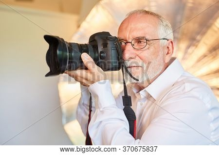 Senior as a photographer with experience in the photo shoot in his studio