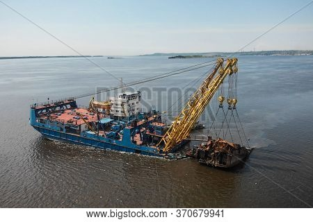 Russia, Saratov - June, 2020. Industrial Ship Crane Removed The Old Sunken Ship From The River