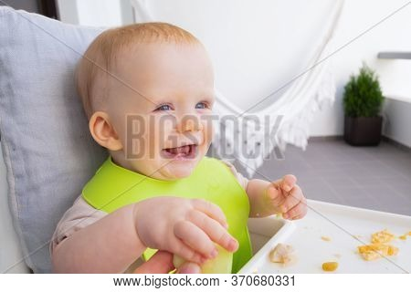 Happy Joyful Baby Girl Taking Slice Of Veg From Mother Hand, Learning To Eat By Her Self. First Soli
