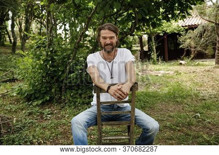 Handsome Mature Man Sitting On A Wooden Chair And Laughing In A Natural Parkland. Bearded And Happy