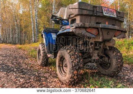 Quad Bike On The Road. A Blue Atv Polaris Quad Bike Stands On The Road In The Autumn Forest. The Suv