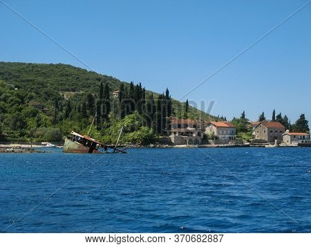 The Remains Of A Sunken Ship In A Bright Blue Sea, Against The Background Of Houses On The Coast At