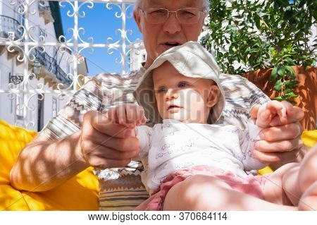 Mature Man Holding Adorable Baby Granddaughter On His Knees On In Street Cafe. Closeup Shot, Low Ang