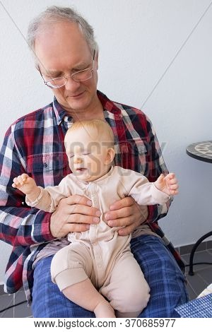 Calm Grey Haired Man Holding Adorable Baby Granddaughter On His Knees. Closeup Shot, Front View. Fam