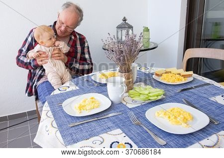 Positive Grandpa Sitting At Dining Table With Food And Holding Baby Granddaughter In Arms. Family Or