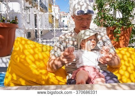Adorable Baby Girl Sitting On Grandfather Knees On Outdoor Terrace Or Street Cafe. Front View. Famil