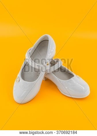Pair Of White Baby Lacquered Girls Shoes At Yellow Background