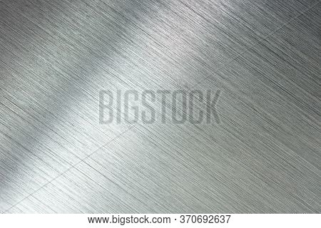 Photograph of brushed metal, or hair line pattern metal. Brushed metal with reflection. Diagonal grain.  High resolution Sharp to the corners.