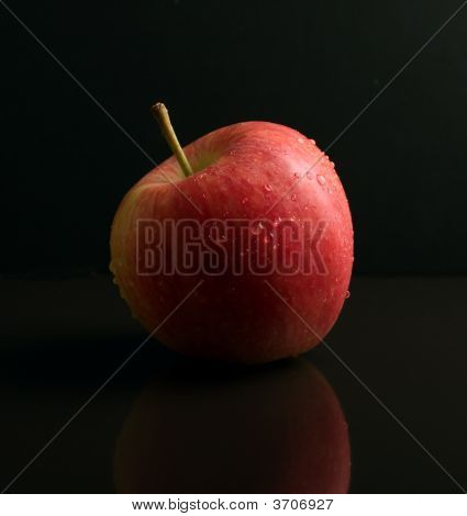 Red Apple On Black Reflective Surface